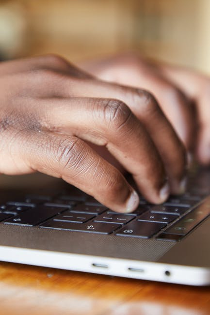 person's hand typing on a keyboard